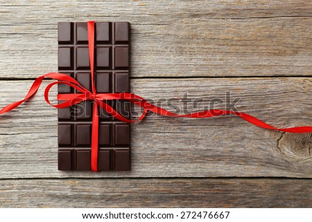 Dark chocolate bar with red bow on grey wooden background - stock photo