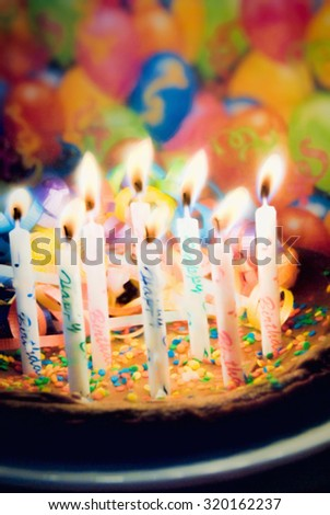 Dark chocolate brownie birthday cake with eight happy birthday burning candles. the cake is covered with sprinkles and chocolate icing. This is computer generated art from a photograph.  - stock photo