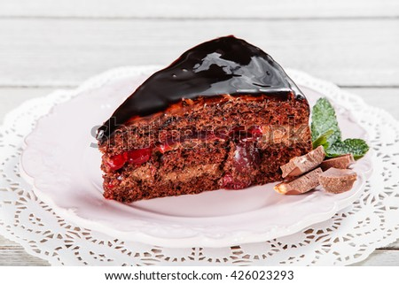 Dark chocolate cake with chocolate cream and icing, with cherries on plate, on a light wooden background. Selective focus - stock photo