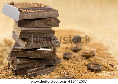 Dark chocolate chunks on burlap texture - stock photo