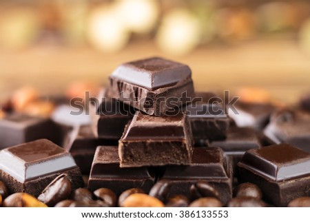 Dark chocolate cubes, coffee beans and peanuts, close-up, soft, selective focus, blurred background - stock photo