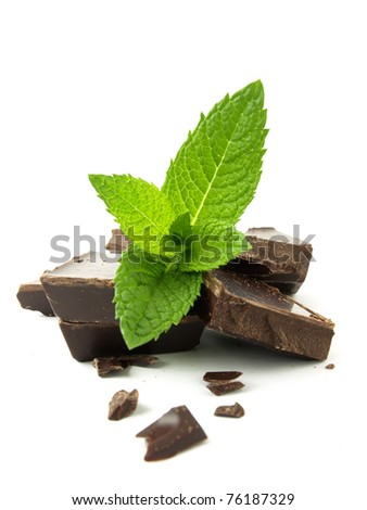 Dark chocolate with mint leaves in the foreground - stock photo
