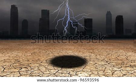 Dark city with hole in desert floor - stock photo