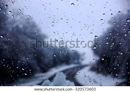 Dark clouds and  snow storm viewed through car window - stock photo