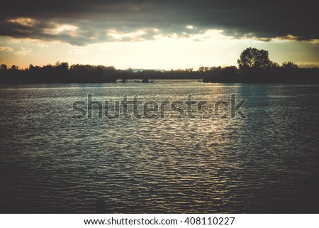 dark clouds at sunset, sunrise above the water surface, filter - stock photo