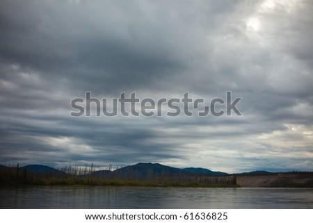 Dark clouds brewing over Yukon River before rain. - stock photo