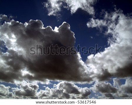 dark clouds in the sunny sky background - stock photo