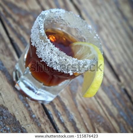 dark colored shot of alcohol with a lemon slice - stock photo
