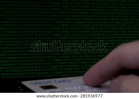 Dark computer screen with green binary code displayed with out of focus computer keyboard with male hand and credit card in foreground. Amongst the number ones and zeroes there is the word SECURITY. - stock photo