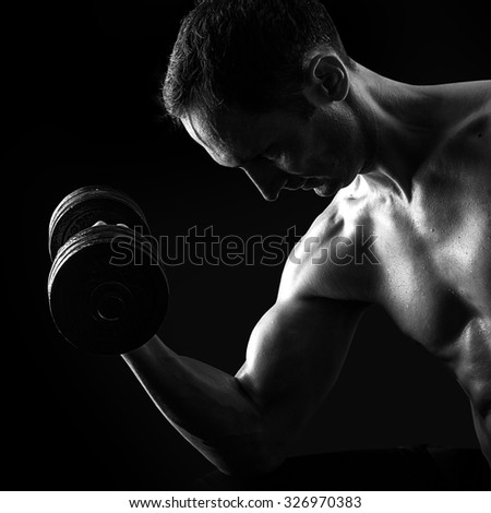 Dark contrast black and white silhouette of young muscular fitness man. Bodybuilder with beads of sweat training in gym. Working out with dumbbells on black background - stock photo