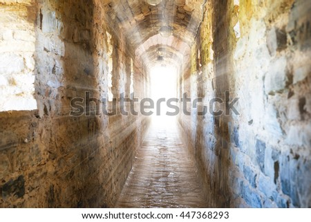 Dark corridor in dungeon with sun rays of light in the end - stock photo
