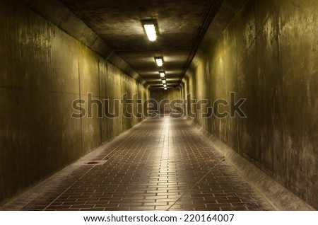 Dark corridor, lit a few lamps, mysterious and dangerous place - stock photo