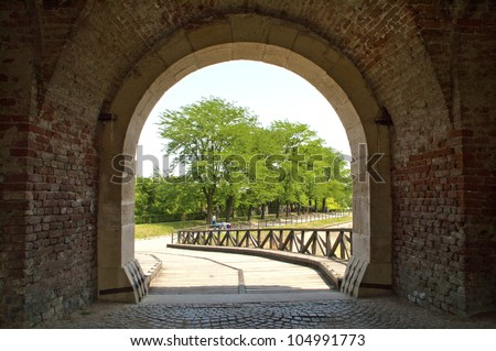 Dark corridor with a arch opening to a beautiful bridge - stock photo