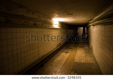 Dark deserted underground tunnel with only one light. - stock photo
