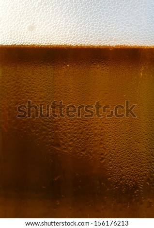 Dark draft beer in a glass mug with condensation on the glass. - stock photo