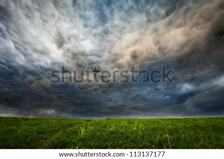 dark dramatic clouds over meadow with green grass and small flowers - stock photo