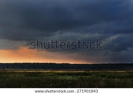 Dark dramatic rain clouds over countryside landscape. Autumn in Latvia. - stock photo