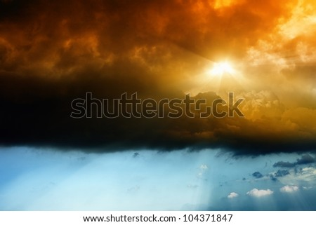 Dark dramatic sky with bright red sun - stock photo