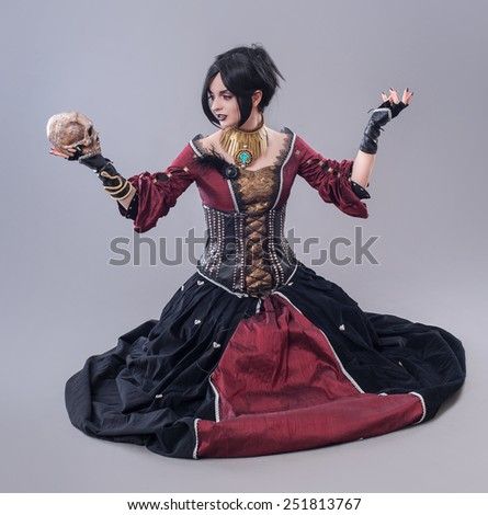 Dark gothic woman. Sexy gothic woman posing with skull. - stock photo