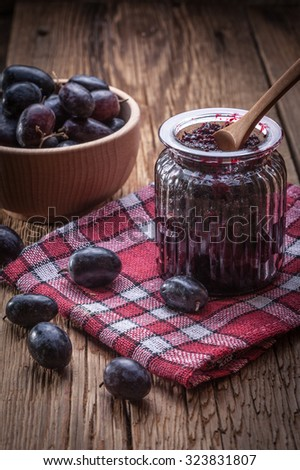 Dark grape jam on a wooden table. - stock photo