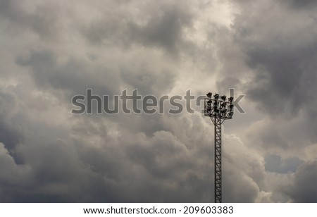 Dark gray clouds in dramatic stormy sky and stadium lights - stock photo