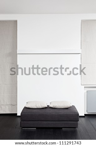 Dark gray padded stool with white pillow, detail of modern sitting room interior in black and white - stock photo