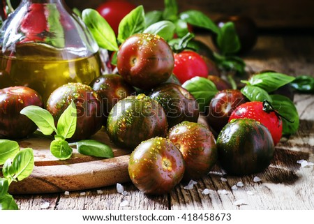 Dark green cherry tomatoes Black Prince, red tomatoes, fresh green basil, extra virgin olive oil in a jug, vintage wooden background, selective focus - stock photo