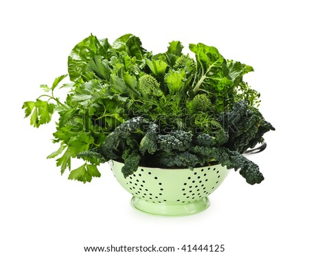 Dark green leafy fresh vegetables in metal colander isolated on white - stock photo