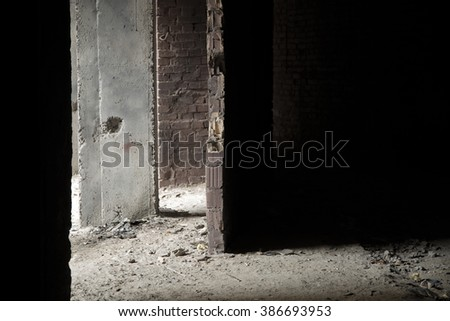 Dark grunge construction. Light falls on the destroyed wall - stock photo