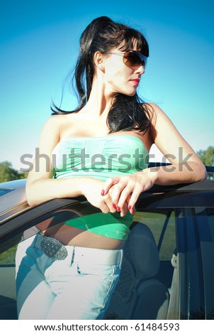 dark-haired girl in glases near the car - stock photo