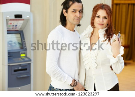 Dark-haired man and red-haired woman stand near to cash dispenser, she holds credit card - stock photo