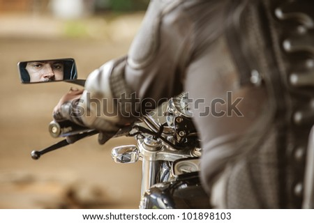 Dark-haired man sitting sitting on his motorcycle. - stock photo