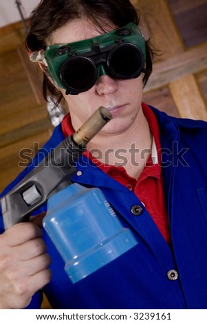 Dark haired man with blue overall holding blowtorch wearing welding goggles - stock photo