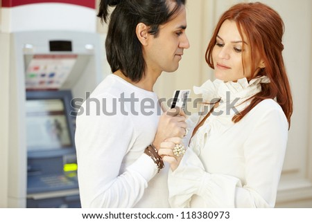 Dark-haired man with credit card in hand and red-haired woman stand face to face, she holds his hand and looks at card - stock photo