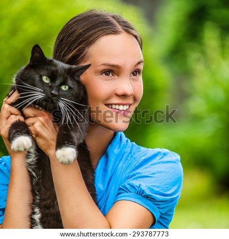 Dark-haired smiling beautiful young woman in blue blouse with black cat, against green of summer park. - stock photo