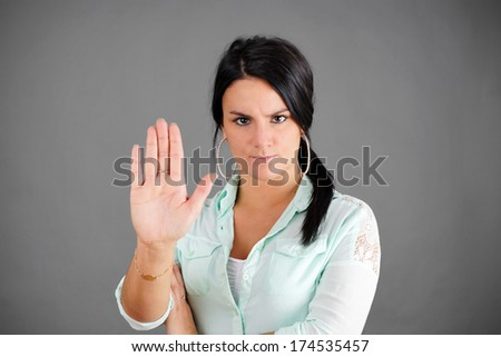 Dark haired woman making NO or STOP gesture with hand, concept       - stock photo