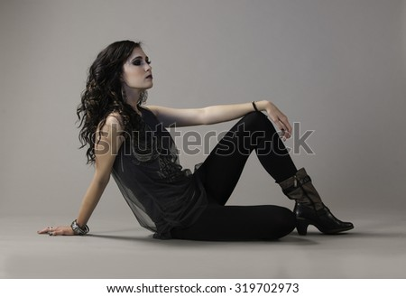 Dark haired woman seated on ground, wearing edgy grunge style outfit leaning with her wrist on her knee. - stock photo