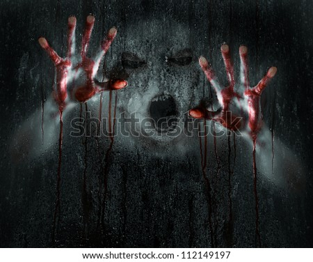 Dark Horror Scene of a Deformed Demon or Zombie with Bloody Hands against Wet Glass - stock photo