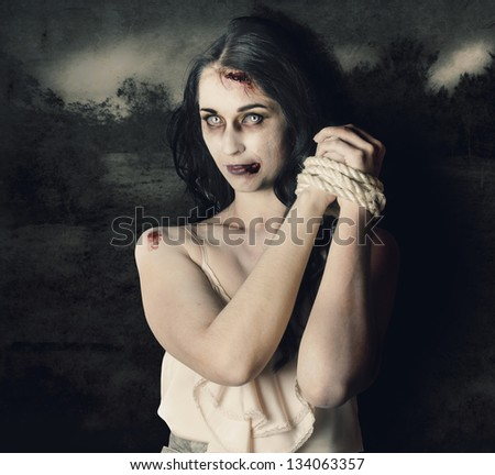 Dark horror scene of an evil zombie woman with hands bound and tied, haunted grunge landscape background - stock photo