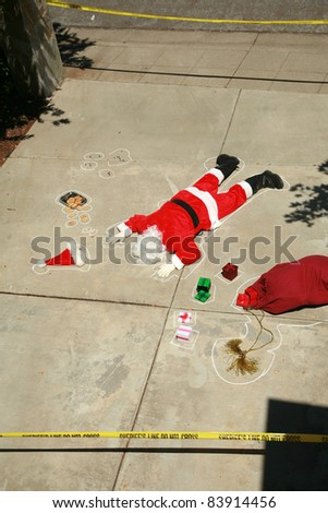 "Dark Humor Series. Santa Claus shot dead in a ""drive by shooting"" . Real Sheriff crime scene tape used in this dramatic scene.  No Santas where harmed in the making of this image series. - stock photo"