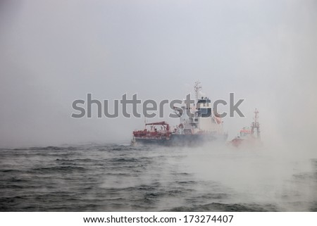 Dark image of ship and boats on sea during a violent blizzard. - stock photo