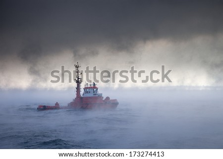 Dark image of ship on sea during a violent blizzard. - stock photo