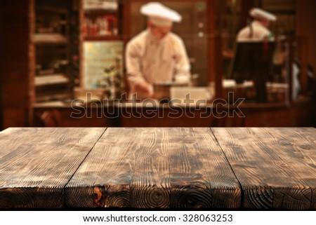dark interior of restaurant with kitchen chef and deck top  - stock photo