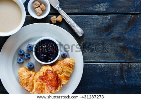 Dark kitchen table with breakfast set. Freshly baked croissant, blueberry jam and coffee on rustic wooden board over dark grunge backdrop, top view. - stock photo