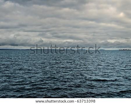 dark lake before storm over rain clouds - stock photo