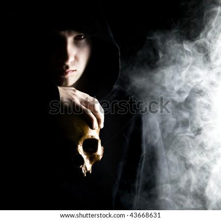 dark man with skull in smoke - stock photo