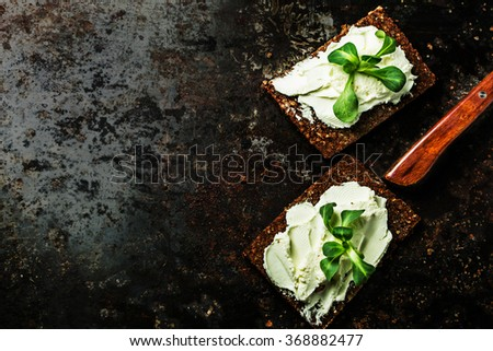 Dark metal surface   rye loaves sandwich with cream cheese and fresh cornsalad. Top view. - stock photo