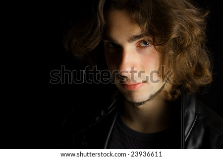 Dark moody portrait on an attractive young man against a black background - stock photo