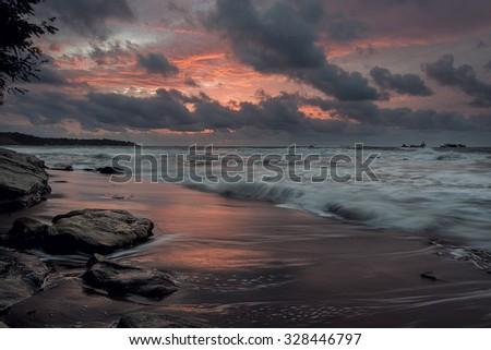 Dark moody sunrise at the beach landscape seascape - stock photo
