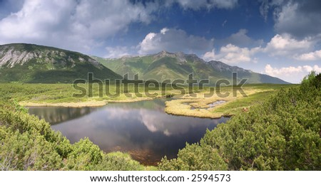 Dark mountain lake with reflections in the water - stock photo
